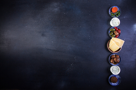 Set collection of cheese and snacks. Grilled halloumi, belper knolle, olives, tzatziki sauce over on deep blue black background. Overhead. Copy Space. Stok Fotoğraf