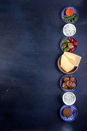 Set collection of cheese and snacks. Grilled halloomi, belper knolle, olives, tzatziki sauce over on deep blue black background. Overhead. Copy Space.