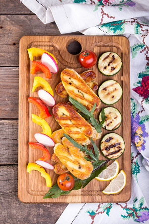 Set collection of cheese and snacks. Grilled halloumi, pepper, zuccini, tomato cherry and radish over on old wooden rustic background. Overhead.