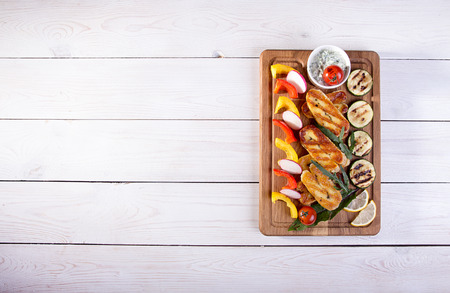 Set collection of cheese and snacks. Grilled halloumi, pepper, zuccini, tomato cherry and radish over on white wooden  background. Overhead. Copy space.