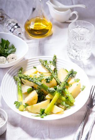 Boiled potato with grilled green asparagus on white plate over onwhite background. Overhead.