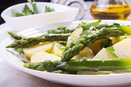 Boiled potato with grilled green asparagus on white plate. Close up.