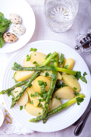 Boiled potato with grilled green asparagus on white plate over on white background. Overhead. Stok Fotoğraf