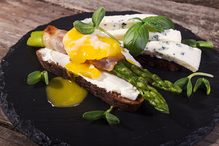 Toast with sticks of grilled green asparagus wrapped with bacon, poached egg , sprouts and blue cheese on black stone slate over on old wooden rustic background.