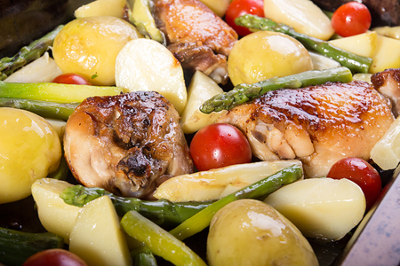 Baked in oven potato, chiken, asparagus, cherry tomato in baking pan.