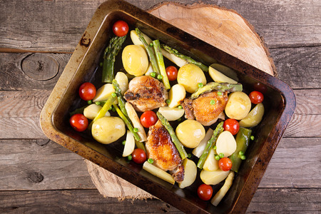 Baked in oven potato, chiken, asparagus, cherry tomato in baking pan over on old wooden rustic background. Overhead. Reklamní fotografie
