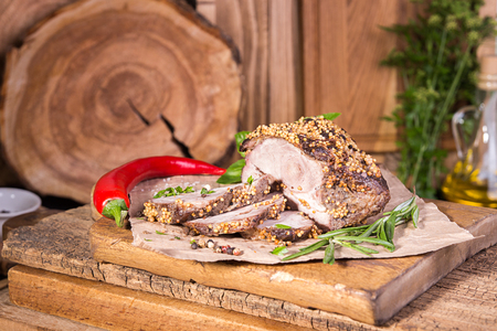 Piece and slices of roasted meat. Cold-boiled baked pork with mustard grains on old wooden background.