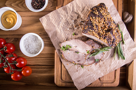 Piece and slices of roasted meat. Cold-boiled baked pork with mustard grains on wooden background. Stock Photo