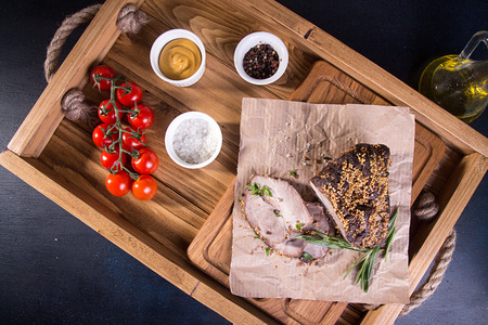 Piece and slices of roasted meat. Cold-boiled baked pork with mustard grains on wooden tray on dark background. Top view.