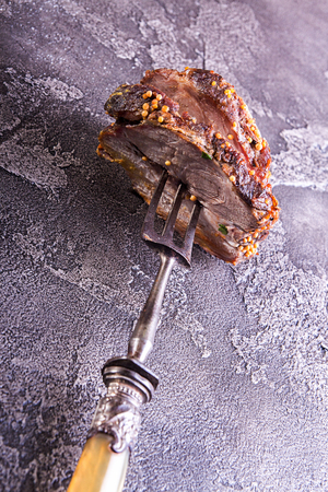 Piece of roasted meat on fork. Cold-boiled baked pork with mustard grains on gray concrete background.