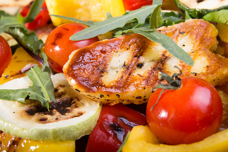 Grilled roasted halloumi cheese with grilled cherry tomato, pepper, zuccini. Tasty snack close up.