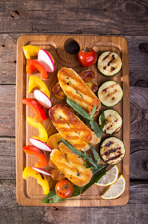 Set collection of cheese and snacks. Grilled halloumi, pepper, zuccini and radish over on old wooden rustic background. Overhead. Stock Photo
