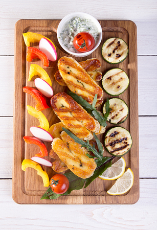 Set collection of cheese and snacks. Grilled halloumi, pepper, zuccini, tomato cherry and radish over on white wooden  background. Overhead. Stock Photo