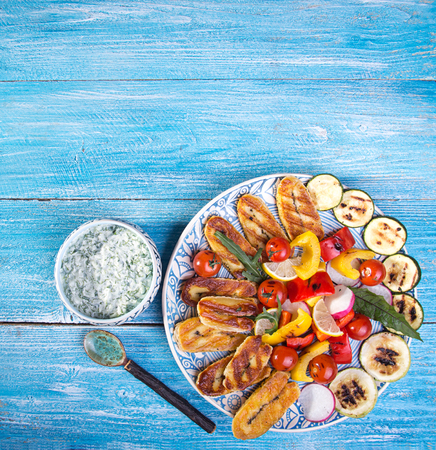Set collection of cheese and snacks. Grilled halloumi, pepper, zuccini, tomato cherry, radish and tzatziki sauce over on blue wooden  background. Overhead. Copy space.