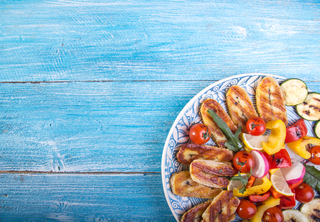 Set collection of cheese and snacks. Grilled halloumi, pepper, zuccini, tomato cherry and radish over on blue wooden  background. Overhead. Copy space.