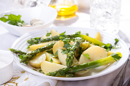 Boiled potato with grilled green asparagus on white plate over on white background. Stock Photo