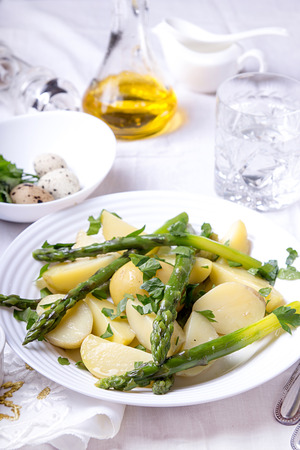 Boiled potato with grilled green asparagus on white plate over on white background. Overhead. Stock Photo