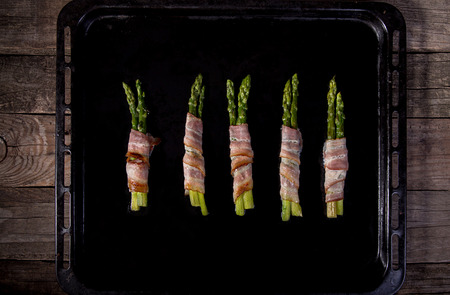 Sticks of green asparagus wrapped with bacon prosciutto ham over on black baking tray background. Overhad. Top view.