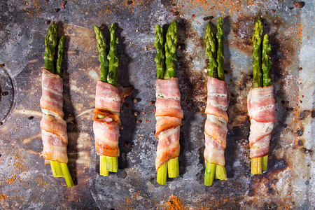 Sticks of green asparagus wrapped with bacon prosciutto ham over on old rusty background. Overhad. Top view.
