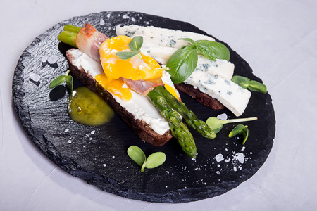 Toast with sticks of grilled green asparagus wrapped with bacon, poached egg , sprouts and blue cheese over on black stone slate background. Gray concrete backdrop.
