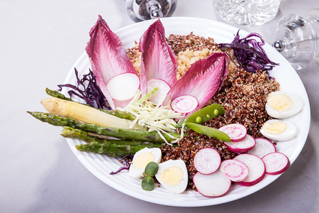 Fresh salad of white and red kino, grilled green asparagus, cabbage, radish, quail eggs, chicory. Overhead.