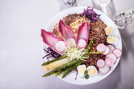 Fresh salad of white and red kino, grilled green asparagus, cabbage, radish, quail eggs, chicory. Overhead. Copy space. Stock Photo