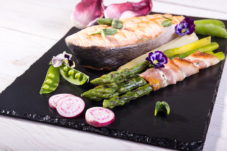 Baked in oven grilled salmon, stick of green asparagus wrapped in bacon on black background. Overhead. Stock Photo