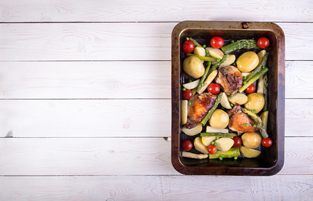 Baked in oven potato, chiken, asparagus, cherry tomato in baking pan over on white wooden background. Overhead. Copy space. Stock Photo