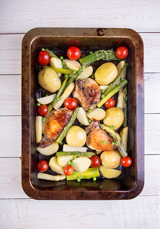 Baked in oven potato, chiken, asparagus, cherry tomato in baking pan over on white background. Overhead. Stock Photo