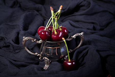Ripe sweet cherries in small metall bowl on blak fabric. Stock Photo