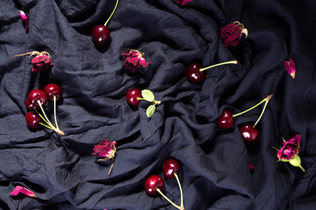 Composition with ripe sweet cherry and dry roses over on black fabric  flat lay. Top view.