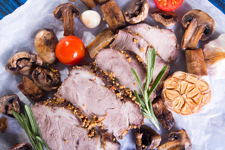 Slices of roasted meat. Cold-boiled pork with mushrooms, garlic and cherry tomato on parchment. Top view Stock Photo