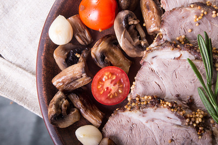 Dinner plate with baked cold-boiled pork meat, fried mushrooms, cherry tomato. Overhead. Stock Photo