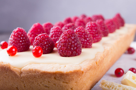 Tarte shortcake with mascarpone, white chocolate and cream served with fresh raspberries and red currant. Stock Photo