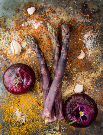 Purple asparagus flat lay. Garlic red onions spices violet flower over on rustic background. Vegetarian dieting organic healthy eating concept.