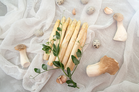 Modern flat lay vegetarian food, overhead white asparagus, quail eggs, oyster mushrooms, garlic, branch of pea blossom on white gauze. Organic dieting healthy food concept.