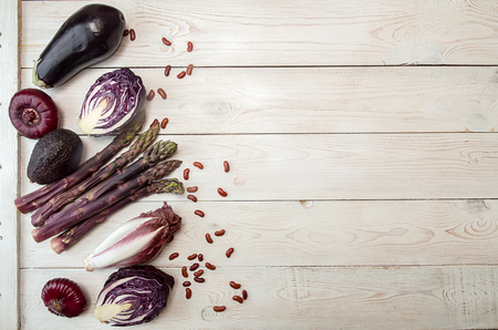 Set collection purple vegetables on white wooden background. Concept healthy eating. Overhead.Copy space.
