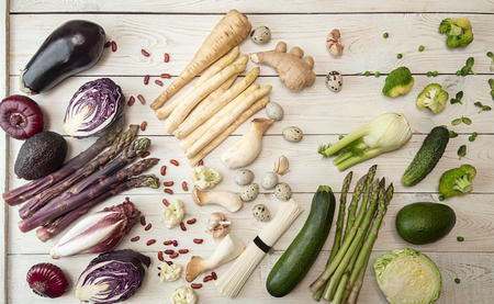 Plant based modern flat lay big set collection rows of white red purple green vegetables on white background. Asparagus, red cabbage, avocado, eggplants, onion. Healthy food concept. Overhead. Top view.