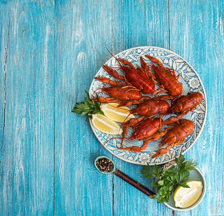 Boiled cooked crayfish crawfish ready to eat on blue plate over on blue wooden background. Copy space. Overhead. Top view. 版權商用圖片