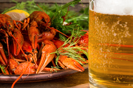 Beer party. Still life with glass of beer, crayfish crawfish against old wooden rustic background. Front view.