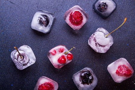 Frozen berries (raspberries, blackberries, blueberries, red currant, cherry) in ice cube over white fabric background. Top view. 版權商用圖片