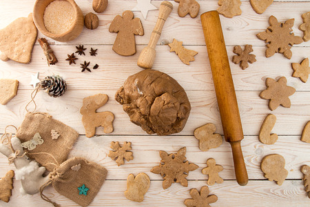 Preparation making traditional Christmas New Year gingerbread cookies. Baked cookies and raw dough on white wooden background 版權商用圖片