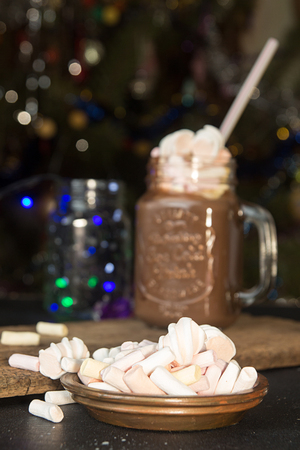 Plate with marshmallow and mug of hot chocolate drink with marshmallow candies on top and lights on Christmas tree and decorations. Selective focus.