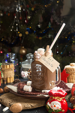 Mug of hot chocolate drink with marshmallow candies on top and lights on Christmas tree and decorations.