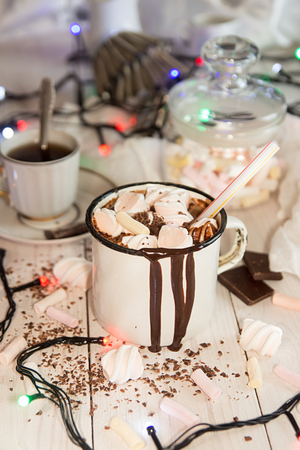 Mug of hot chocolate drink with marshmallow candies on top and candles and Christmas lights.