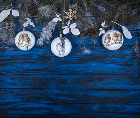 Christmas New Year background. Christmas balls, branches of Christmas tree on blue wooden background. Top view. Copy space.