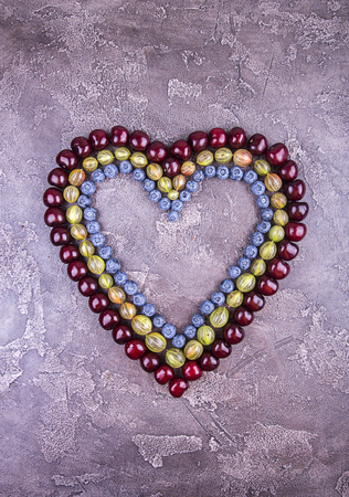 Fresh sweet cherries, blueberry and goosberry in heart shape over on concrete gray background. Top view. Copy space.