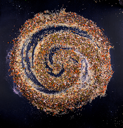 Food background. Swirl of various Legumes, sereals, beans, grain and seeds on dark background. Kind of lentils, bulgur, mash, chickpeas, sunflower seeds, couscous, rice.