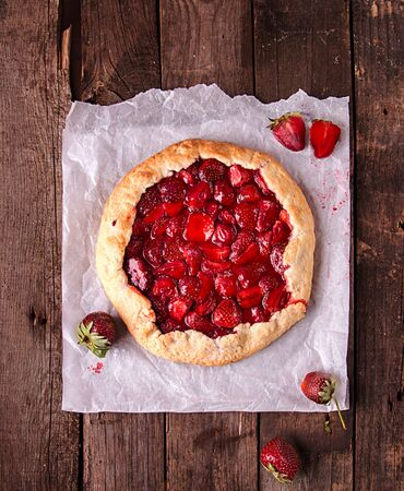 Summer strawberry pie cake galette over on wooden rustic background. Top view Imagens