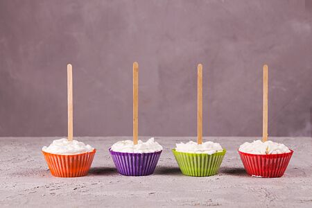 Row of ice cream lollies with whipped cream frozen in muffin molds on gray background. Copy space